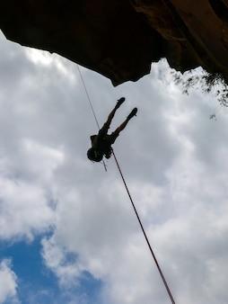 Abseilen van een negatieve sanstone rotswand met blauwe lucht - uitzicht vanaf hieronder