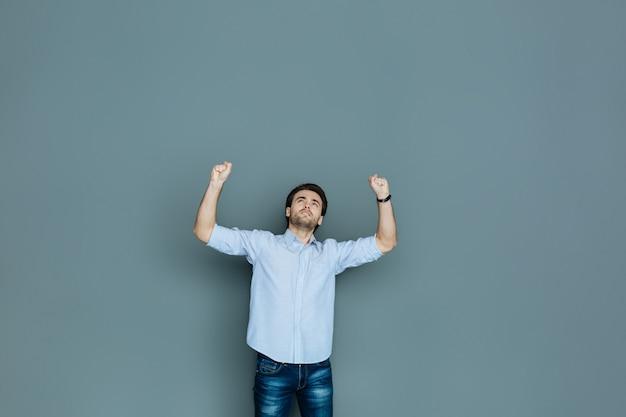 Absoluut succes. leuke positieve opgetogen man die zijn handen omhoog houdt en glimlacht terwijl hij zijn emoties uitdrukt