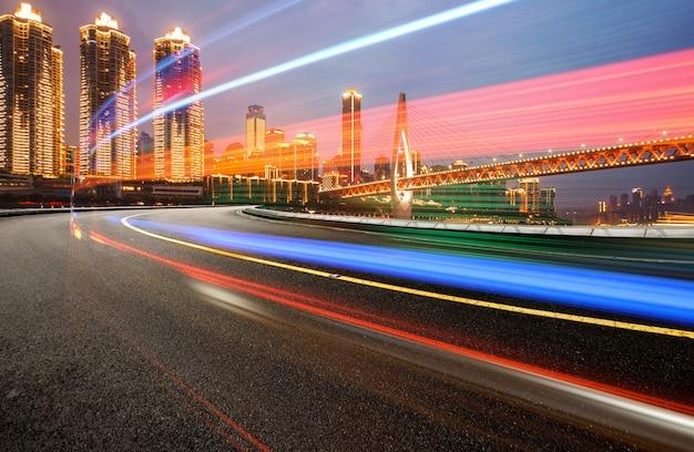Abstract beeld van onduidelijk beeldmotie van auto's op de stadsweg bij nacht, moderne stedelijke architectuur in chongqing, china
