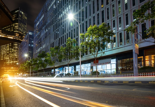 Abstract beeld van onduidelijk beeldmotie van auto's op de stadsweg bij nacht, moderne stedelijke architectuur