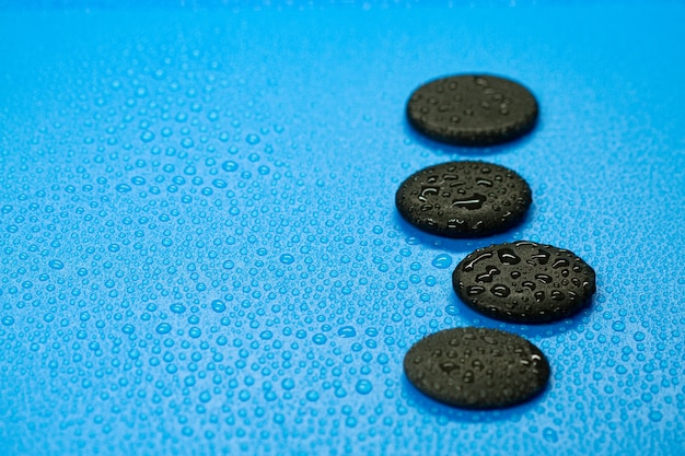 Abstract kuuroordontwerp van waterdalingen en zwarte saldostenen op blauwe achtergrond