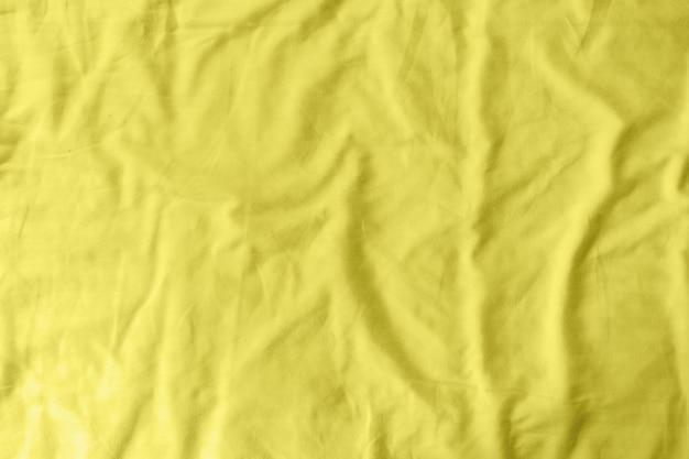 Abstract patroon van een geel verfrommeld laken in een hotelkamer. bij de productie van laken worden katoen, linnen, zijde-modal en bamboe rayon gebruikt. trendy kleur van het jaar 2021 - verhelderend geel