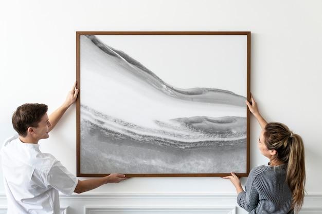 Abstract schilderij wordt opgehangen door een stel