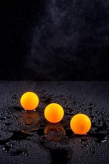 Abstract stilleven met drie oranje ballen onder druppelirrigatie met water