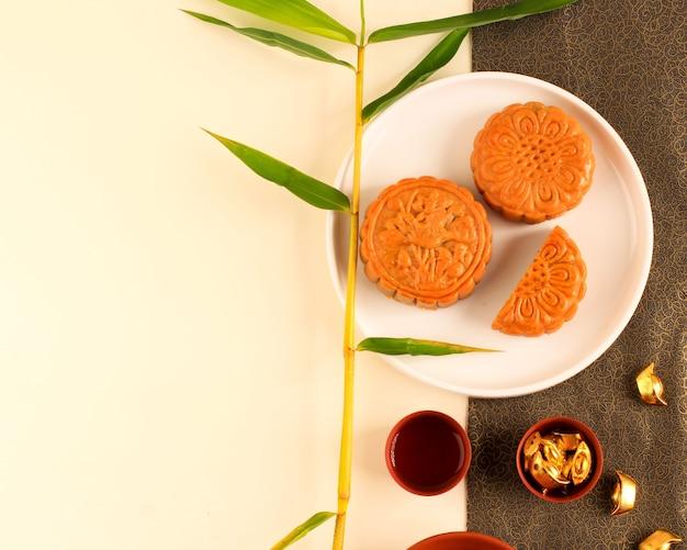 Abstract stilleven mid herfst festival snack en drankje maan cake op crème en zwart gouden achtergrond