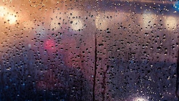 Abstract verkeer in regenende dag. uitzicht vanaf autostoel. regenachtige dagen, regendruppels op het raam, regenachtig weer, regen en bokeh