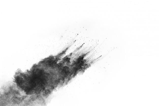 Abstract zwart poeder dat op witte achtergrond wordt gespleten.