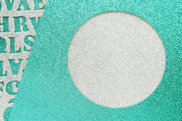 Abstracte achtergrond en textuur van blauwe en zilveren materialen met een glitter met een gebeeldhouwd rond gat en gebeeldhouwde letters.