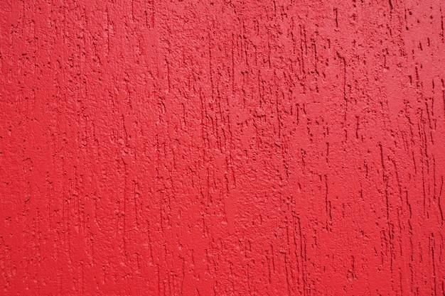 Abstracte achtergrond en textuur van een gepleisterde muur in helder rood met de textuur van de schorskever