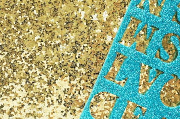 Abstracte achtergrond en textuur van goud materiaal met grote glitter en glanzend blauw materiaal met gebeeldhouwde letters bovenop.