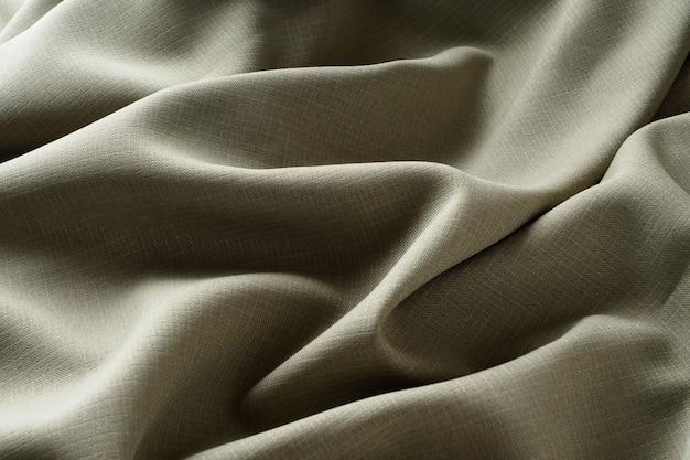 Abstracte achtergrond, grijze luxe stof ligt in golvende plooien, close-up. elegant ontwerp. textuurstof glinstert in het zachte licht. zijdeachtige, gekreukte, donkere stof.