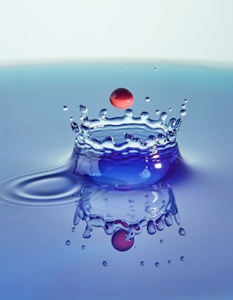 Abstracte achtergrond kleur water splash, botsing van gekleurde druppels en kroon creatie