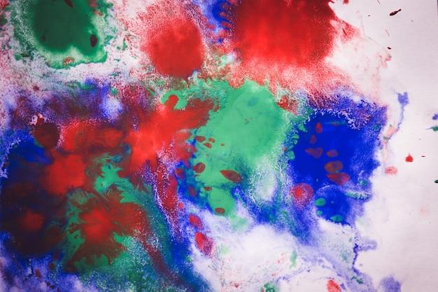 Abstracte achtergrond met vlekken en verspreidt druppeltjes van verschillende kleuren op papier close-up, filter