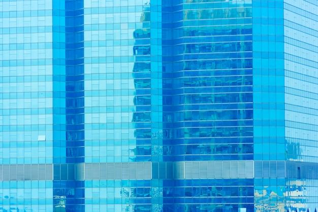 Abstracte achtergrond van blauw brilvenster op de moderne bouw met weerspiegeling van blauwe hemel.