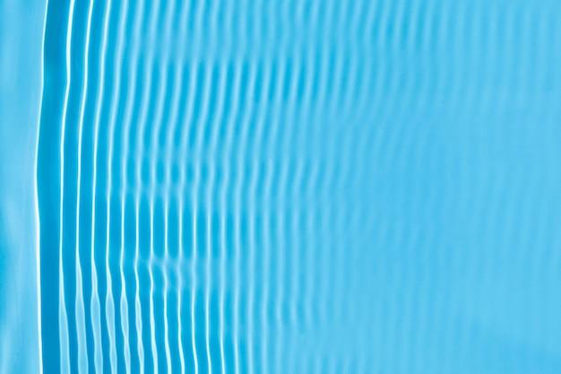 Abstracte achtergrond van blauw water onder zonlicht. bovenaanzicht, plat gelegd.