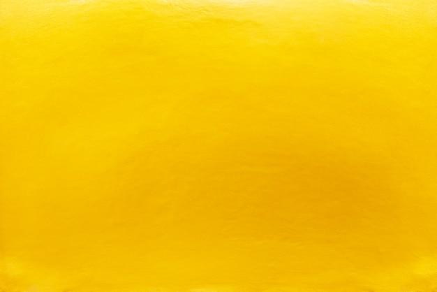 Abstracte achtergrond van goud geschilderd op betonnen muur.