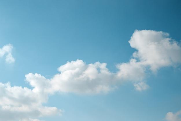 Abstracte achtergrond van lichtblauwe hemel en diagonale pluizige wolk.
