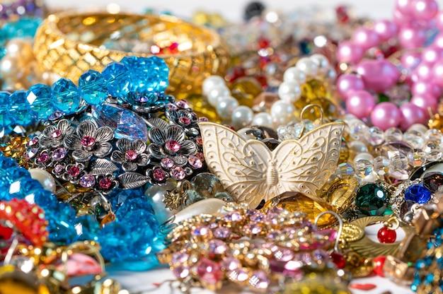 Abstracte achtergrond van verschillende kleurrijke heldere sieraden en kostuumjuwelen, zachte, selectieve focus