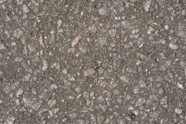Abstracte achtergrond van zwart asfalt met insluitsels van keien