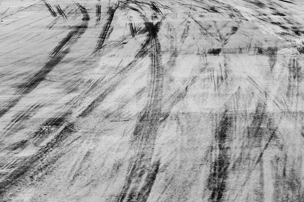 Abstracte achtergrond zwarte bandensporen op cementweg, bandtekens op cementweg.