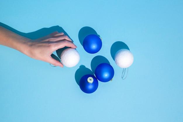 Abstracte afbeelding hand houdt kerstboomversieringen op een blauwe achtergrond. plat lag, bovenaanzicht.