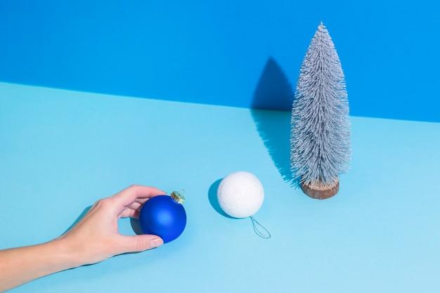 Abstracte afbeelding hand houdt kerstboomversieringen op een blauwe achtergrond.