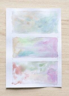 Abstracte aquarel vlekken achtergrond op witboek blad met houten achtergrond. detailopname.