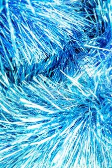 Abstracte blauwe bokeh intreepupil achtergrond. nieuwjaar achtergrondfoto met gloeiend blauw klatergoud. close-up van glanzende metaaltextuur van vakantiedecoratie. de glitterende fonkelende abstracte blauwe bokeh defocused