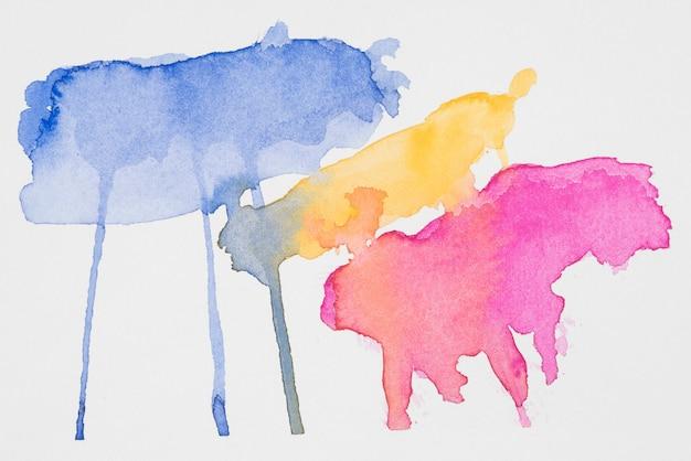 Abstracte blauwe, gele en roze vlekken van verven op wit papier