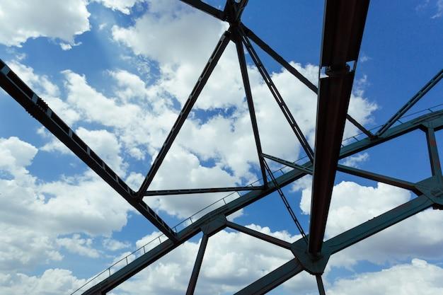 Abstracte brugconstructies op de achtergrond van wolken en blauwe hemel.