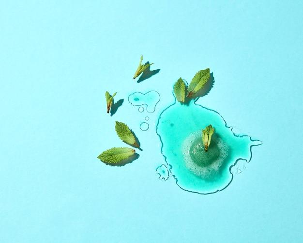Abstracte compositie van gesmolten ijs op een blauwe glazen achtergrond met muntblaadjes duidelijk grenzen en reflectie. bovenaanzicht