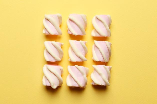 Abstracte compositie van marshmallows op een gele achtergrond. tov weergave