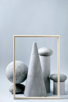 Abstracte compositie van verschillende grijze geometrische objecten, afbeeldingsframe en stenen. kopieer ruimte. modern concept voor productpresentatie.