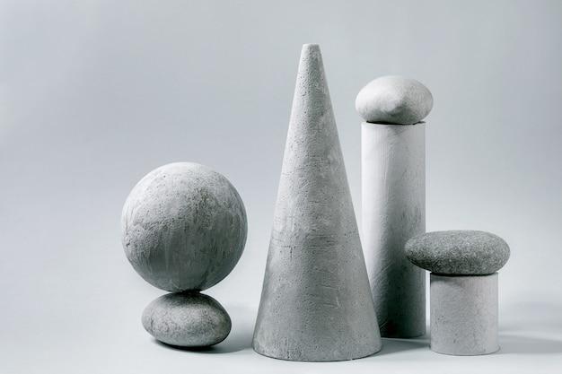 Abstracte compositie van verschillende grijze geometrische objecten en stenen. kopieer ruimte. modern concept voor productpresentatie.