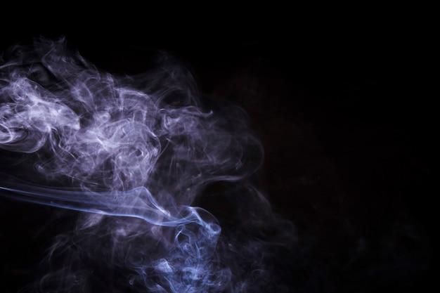 Abstracte dampen van rook tegen zwarte achtergrond