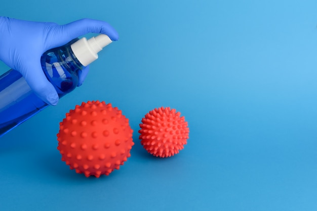 Abstracte desinfectie van het coronavirus. het virus bestrijden met een antisepticum. een hand in een rubberen medische handschoen desinfecteert twee moleculen van het coronavirus met een antisepticum. blauwe chirurgische handschoen. kopieer ruimte.