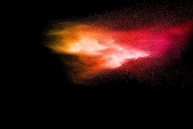 Abstracte explosie van rood stof op zwarte achtergrond.