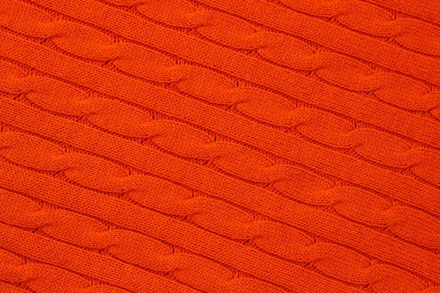 Abstracte fel oranje gebreide achtergrond. garenpatroon, jersey oppervlak, gebreid behang. sieraad van acryl vlechten. wollen weefsel.