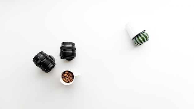 Abstracte foto met camera lenzen koffie en cactus plant zijwaarts