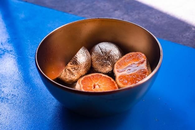 Abstracte fotografie van met metaal beklede mandarijnen in een kom op een blauw en houten oppervlak