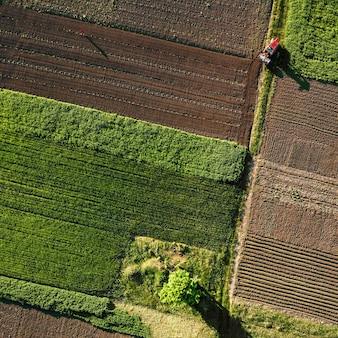 Abstracte geometrische vormen van landbouwvelden met verschillende gewassen en grond zonder inzaaien van gewassen, gescheiden door weg en tractor erop, in groene en zwarte kleuren. een vogelperspectief vanaf de drone.