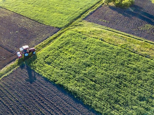 Abstracte geometrische vormen van landbouwvelden met verschillende gewassen en grond zonder inzaaien van gewassen, gescheiden door weg en tractor erop, in groene en zwarte kleuren. luchtfoto van de drone.