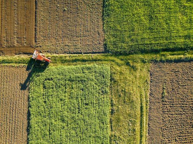 Abstracte geometrische vormen van landbouwvelden met verschillende gewassen en grond zonder inzaaien van gewassen, gescheiden door weg en tractor erop, in groene en zwarte kleuren.