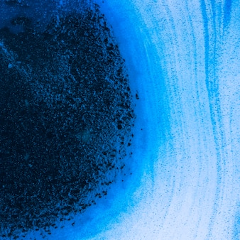 Abstracte golven van schuim en bellen op blauwe vloeistof