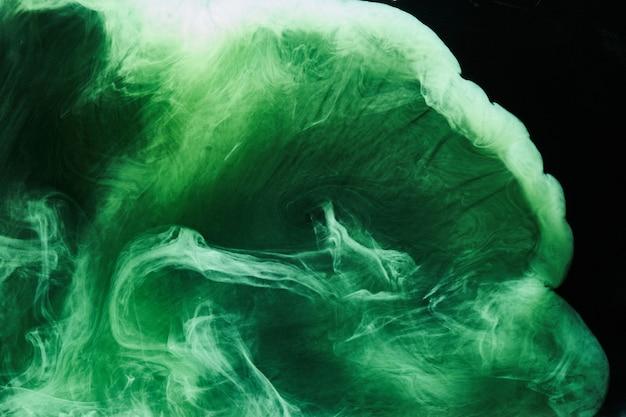 Abstracte groene kleur achtergrond. wervelende levendige waterpijprook, smaragdgroene oceaan onder water, dynamische verf in water