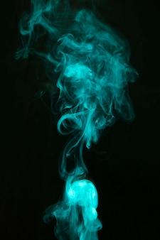 Abstracte groene rook verspreid over de zwarte achtergrond