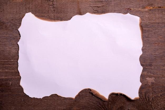 Abstracte grungeachtergrond. oude gebroken horizontale vel papier op bruin houten bord met lege ruimte voor tekst.