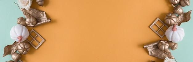 Abstracte herfstachtergrond met gouden pompoenen, bladeren, eikels op gekleurde papieren achtergronden met kopieerruimte in bannerformaat