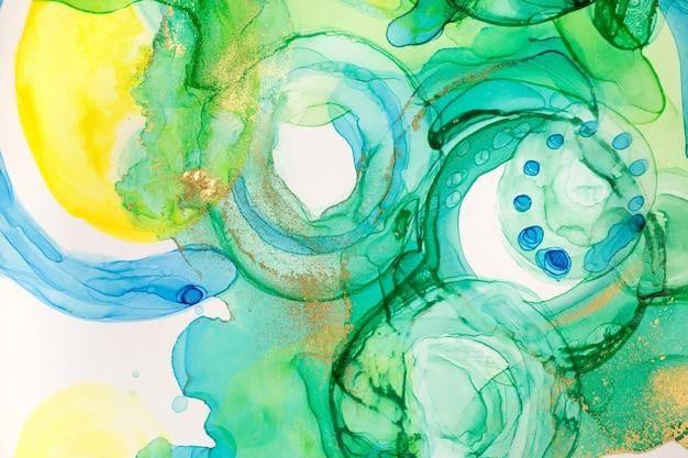 Abstracte inkt blauw groene en gele aquarel inkt druppels achtergrond alcohol inkt