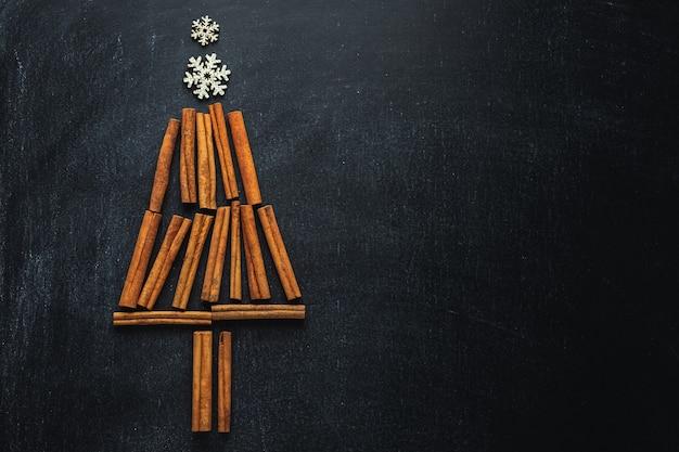 Abstracte kerstboom met pijpjes kaneel en sneeuwvlokken op donkere achtergrond. kerst concept
